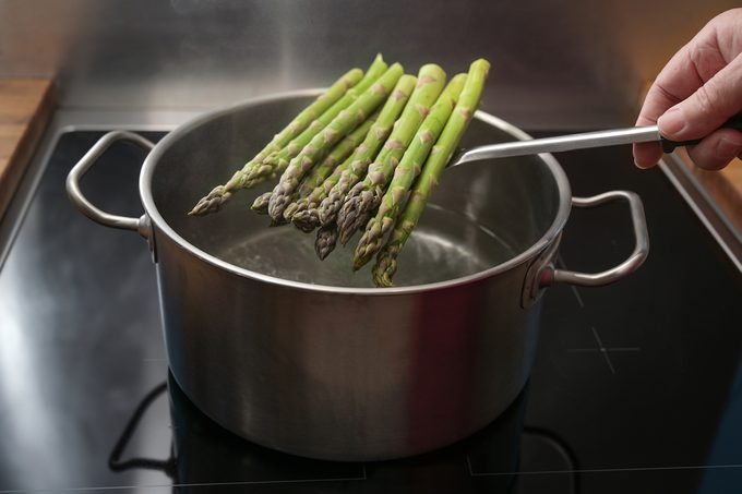 A person holding a pile of asparagus over a boiling pot of water.