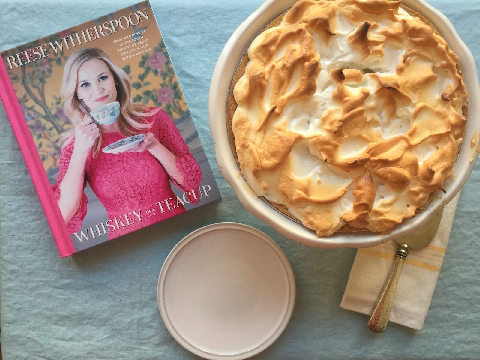 Reese Witherspoon's Whiskey in a Teacup with a Lemon Meringue Pie and plate