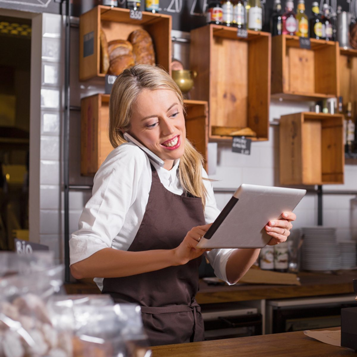 Female barista talking on the phone and using tablet while standing behind the counter