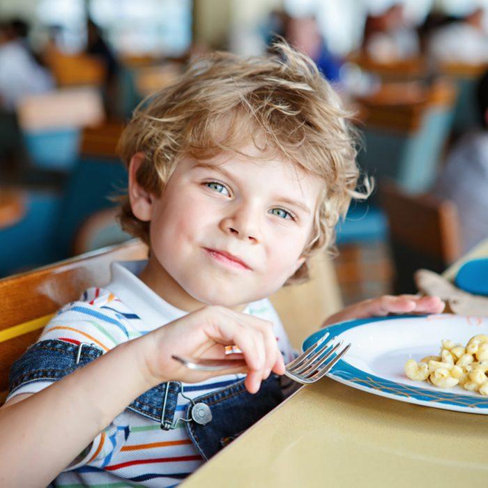 Cute healthy preschool kid boy eats pasta noodles sitting in school or nursery cafe.
