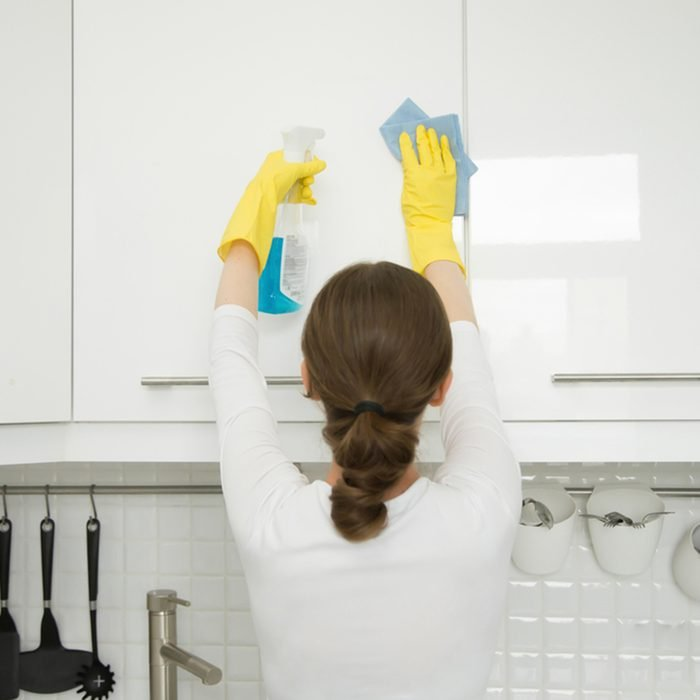 Rear view at an attractive young woman cleaning a surface of white kitchen wall cabinet, wearing rubber protective yellow gloves, with rag and spray bottle detergent.
