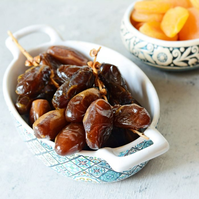 Bowls with juicy dates on a branch and dried apricots on a gray-blue background.