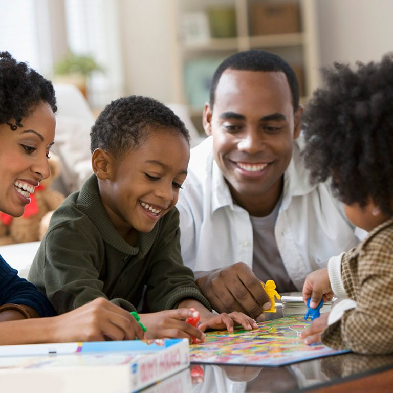 African American family playing board game together crop