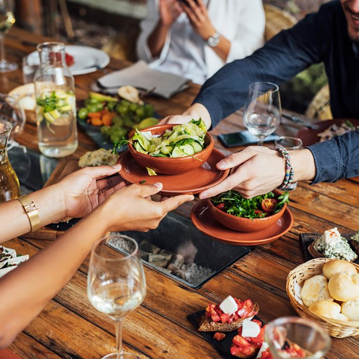 Hands of cropped unrecognisable woman and man passing salad bowl at vegetarian restaurant.