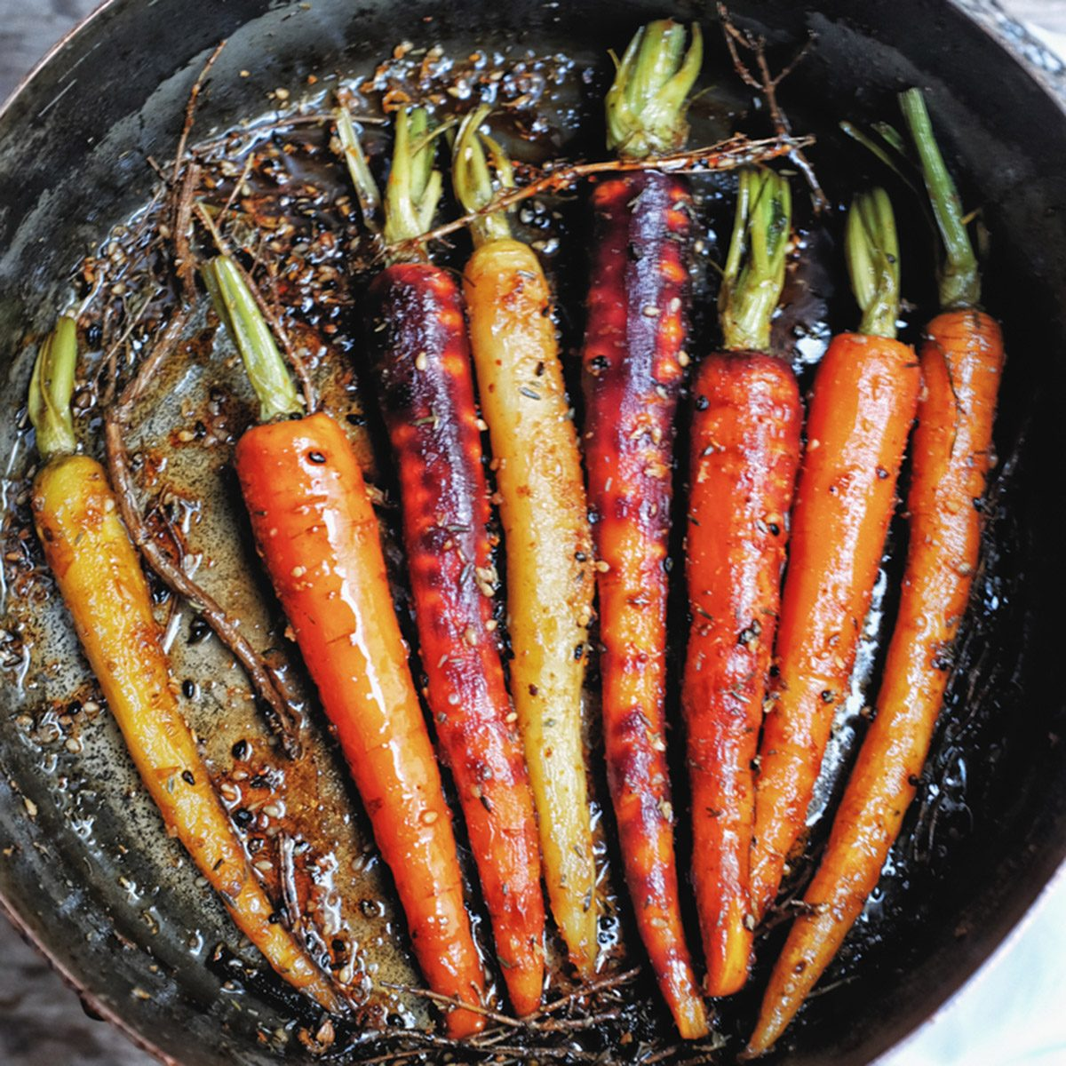 Grilled colorful rainbow carrot in sesame Teriyaki and Mirin sauce, mix herbs, thyme, and Japanese spices in traditional copper pot.