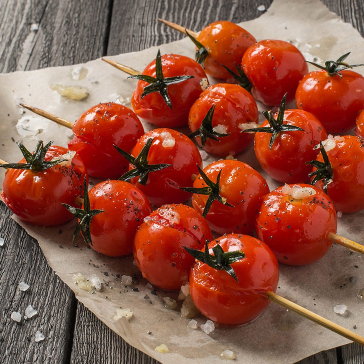 Cherry tomatoes grilled on skewers, lay on baking paper.