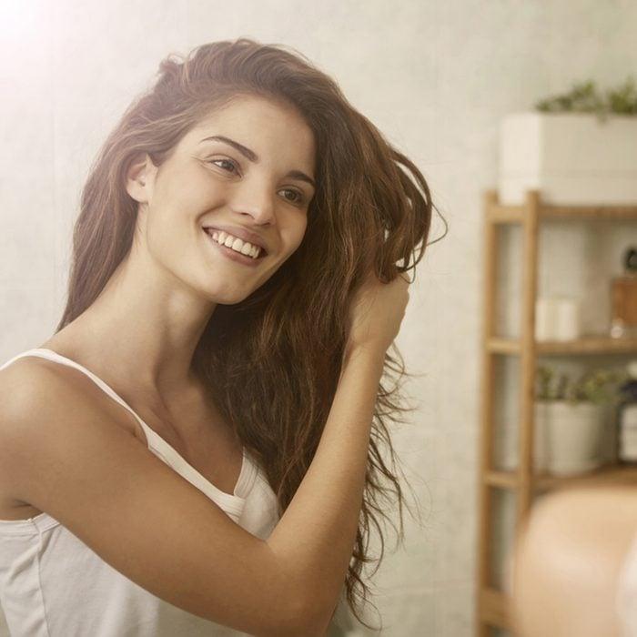 Menina tocando seu cabelo e sorrindo enquanto se olha no espelho