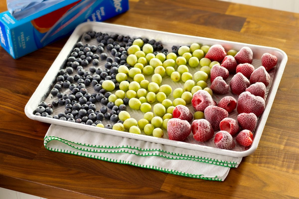 A baking sheet filled with froze blueberries, green grapes and strawberries.