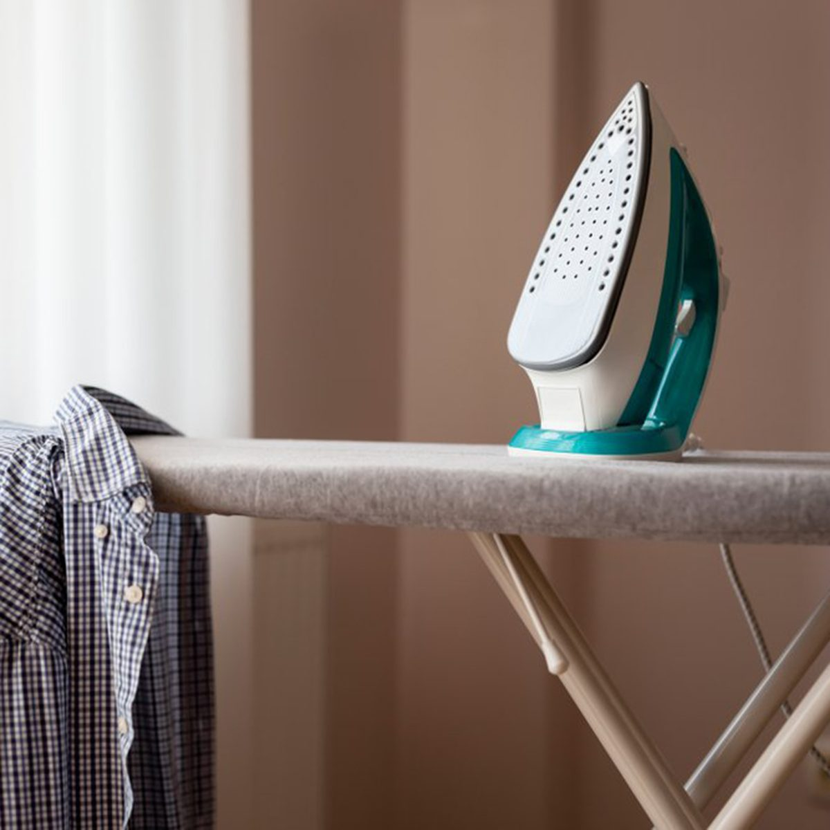 Iron on ironing board with shirt