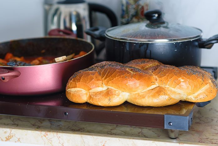 Hot plate for the Sabbath, a pot of spicy fish cooked with peppers and tomatoes, pot of cholent or Hamin in hebrew and challah-special bread in Jewish cuisine. Traditional food for Jewish Shabbat.