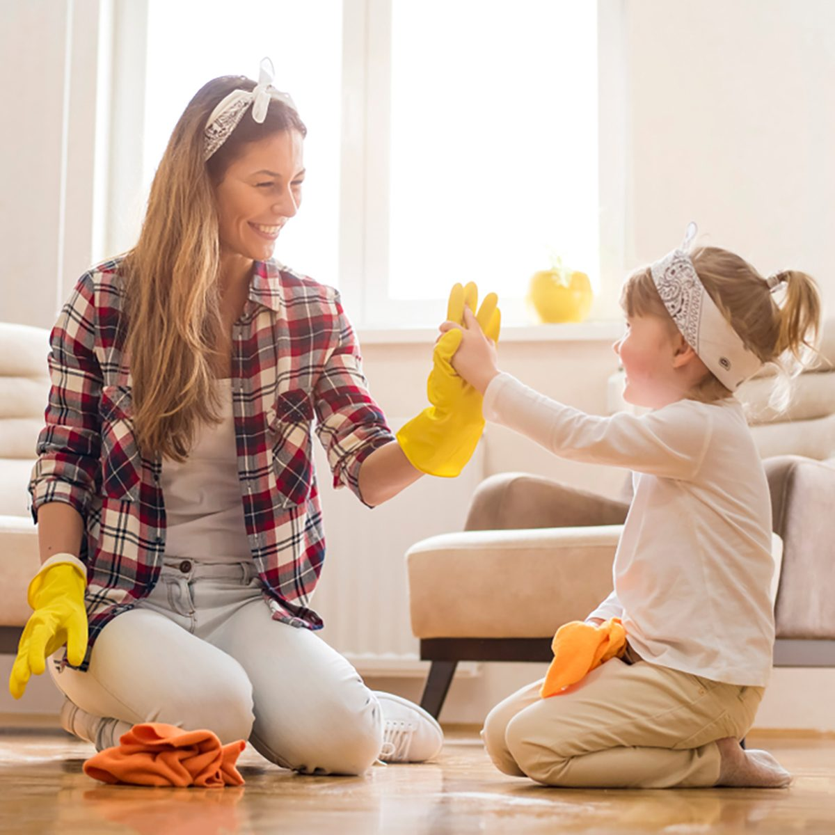Daughter and mother cleaning home together and having fun