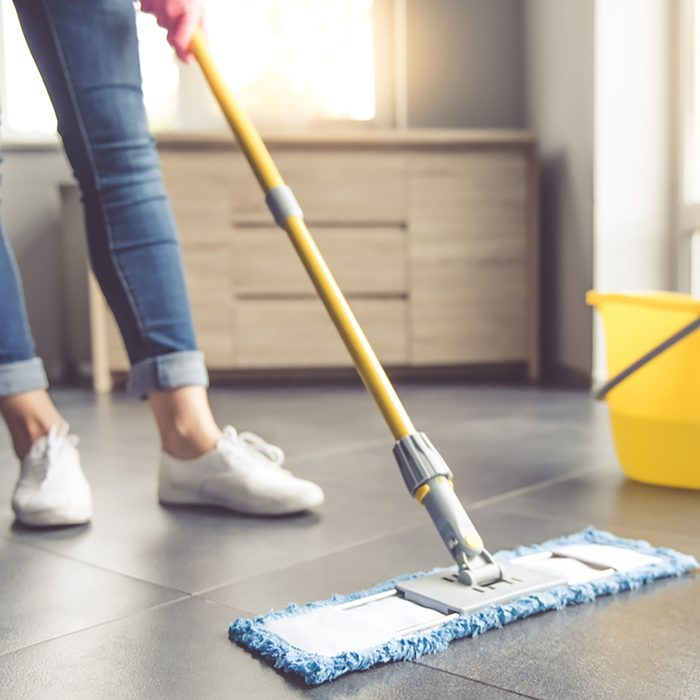 Cropped image of beautiful young woman in protective gloves using a flat wet-mop while cleaning floor in the house;