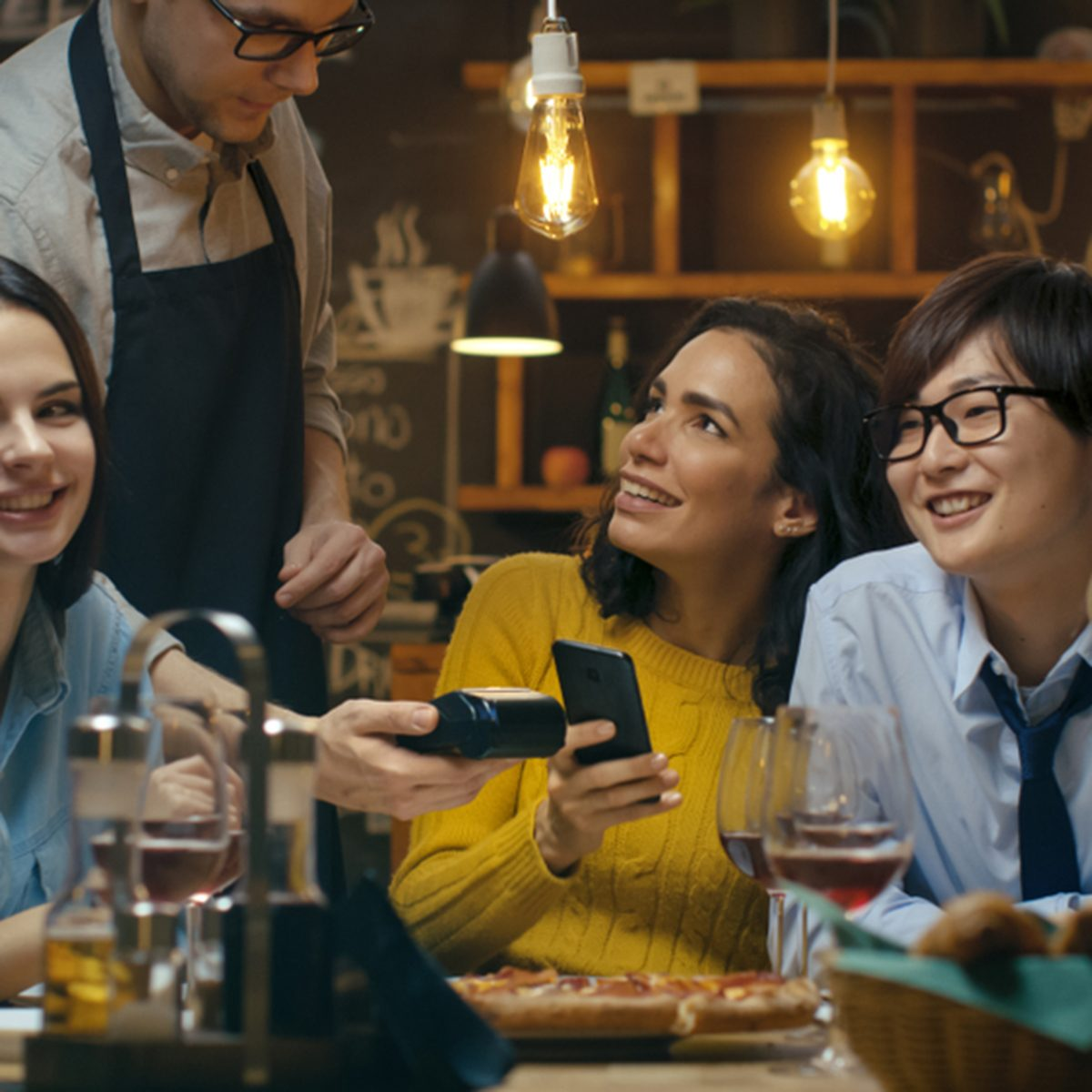 In the Bar Waiter Holds Credit Card Payment Machine and Beautiful Woman Pays for Her Order with Contactless Mobile Phone Payments System.