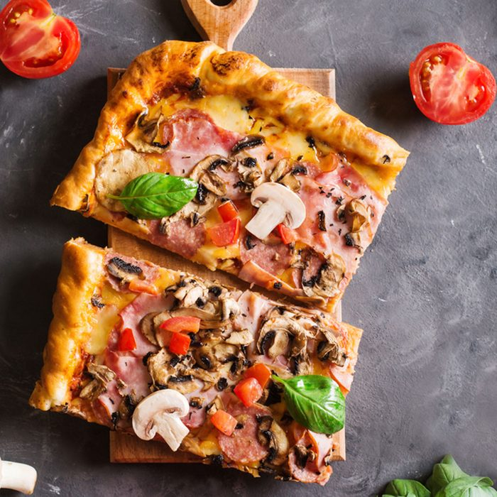 a slice of square pizza with basil tomatoes and mushrooms on a wooden board.