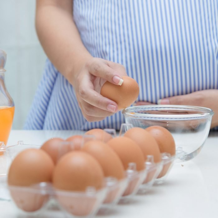 Pregnant woman preparing meal at table in the kitchen,healthy nutrition during pregnancy