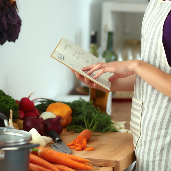 Young woman reading cookbook in the kitchen, looking for recipe