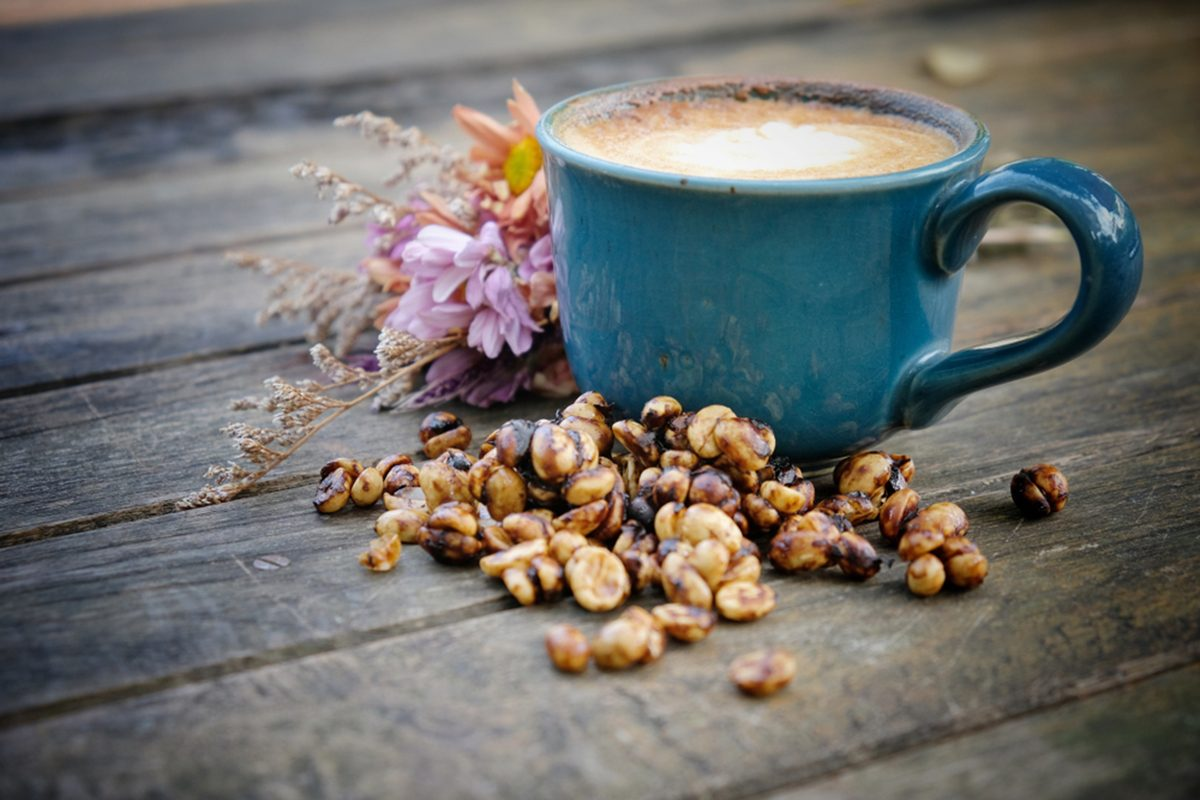 Black honey process coffee, Hot latte on an old wooden background, vintage stye.