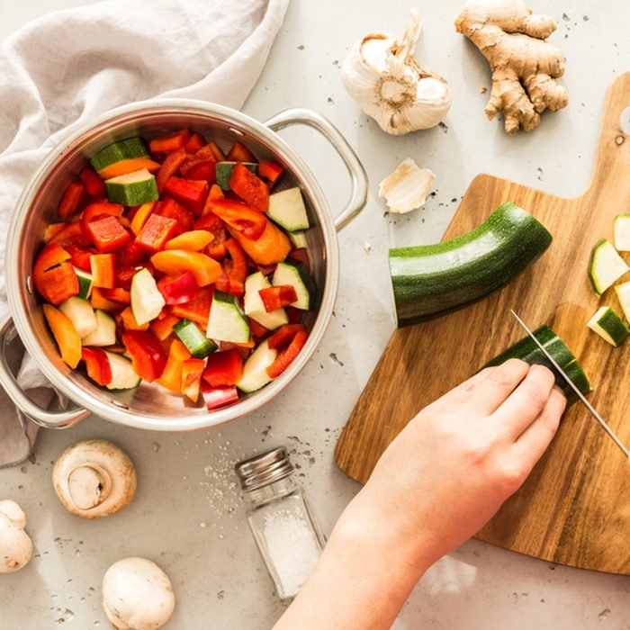 Cooking - chef's hands preparing vegetable vegetarian stew (thick soup). Kitchen scenery - pot with recipe ingredients around on the grey stone worktop captured from above (top view, flat lay). ; Shutterstock ID 1034866882; Job (TFH, TOH, RD, BNB, CWM, CM): TOH