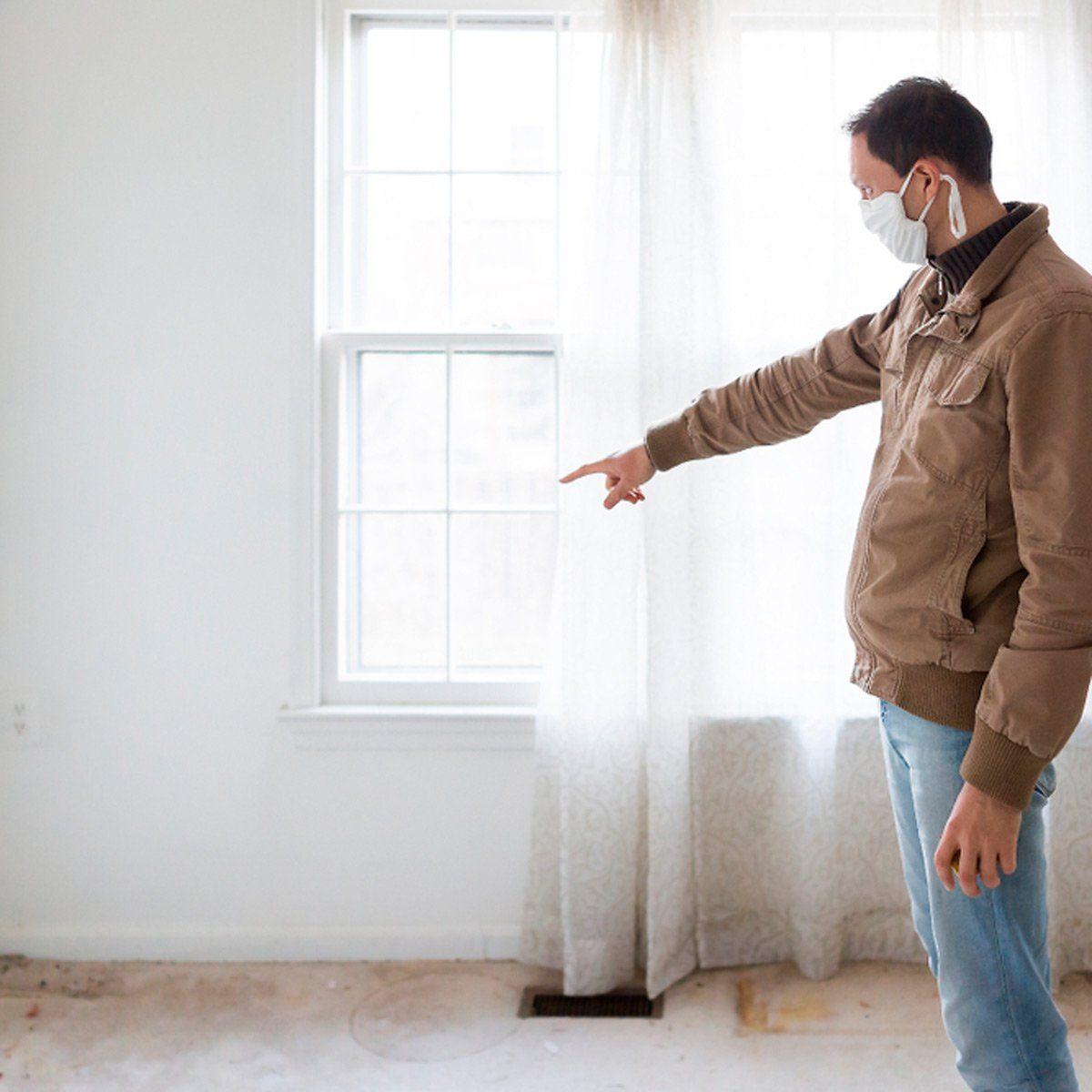 Man pointing at window