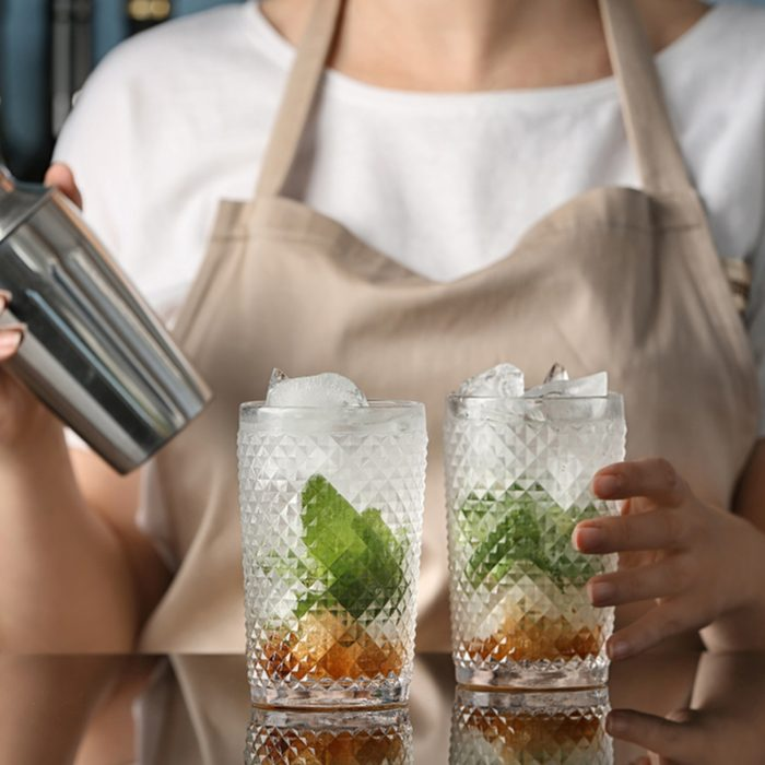 Bartender preparing delicious mint julep cocktail at table