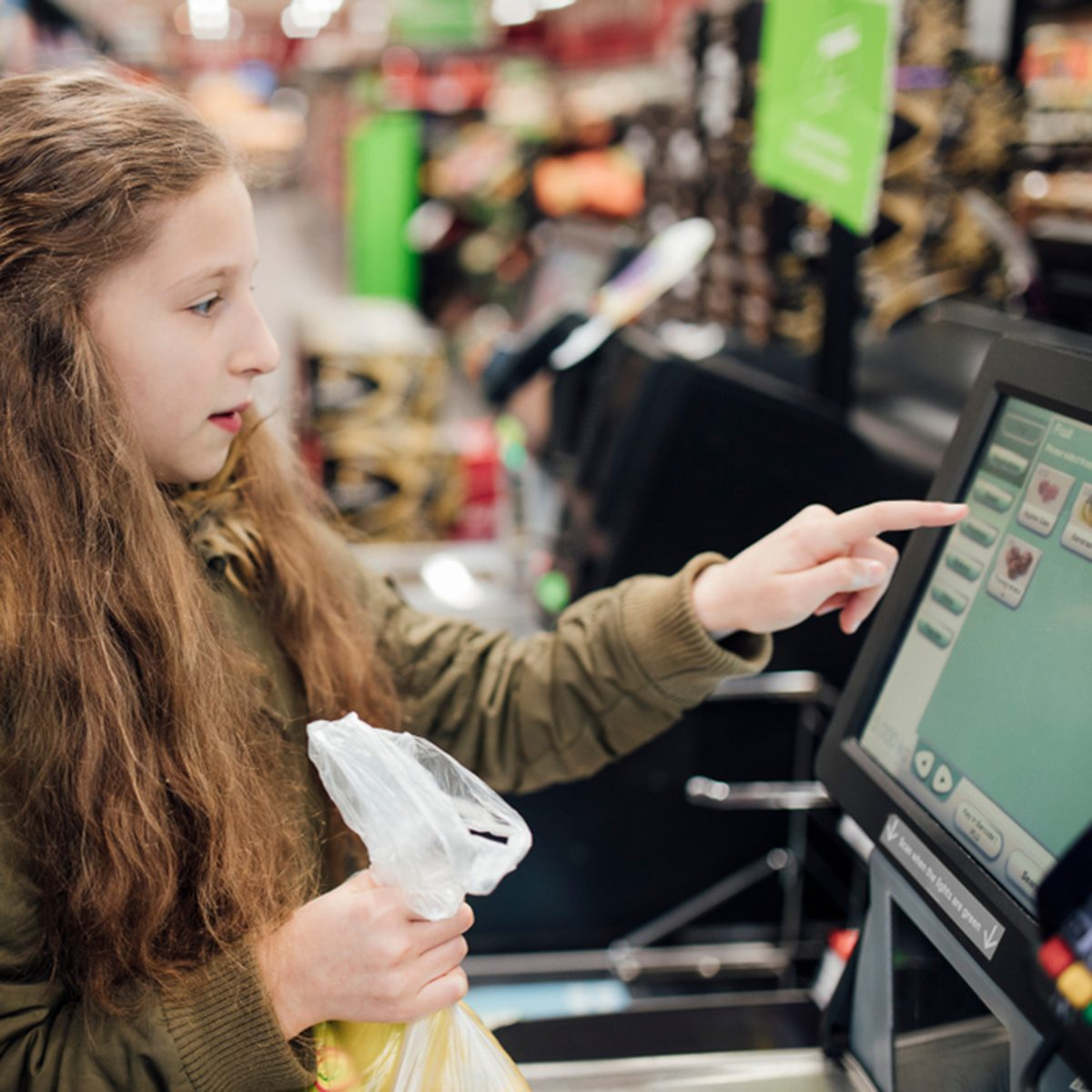 Little girl is at the self service checkout of the supermarket with her father.