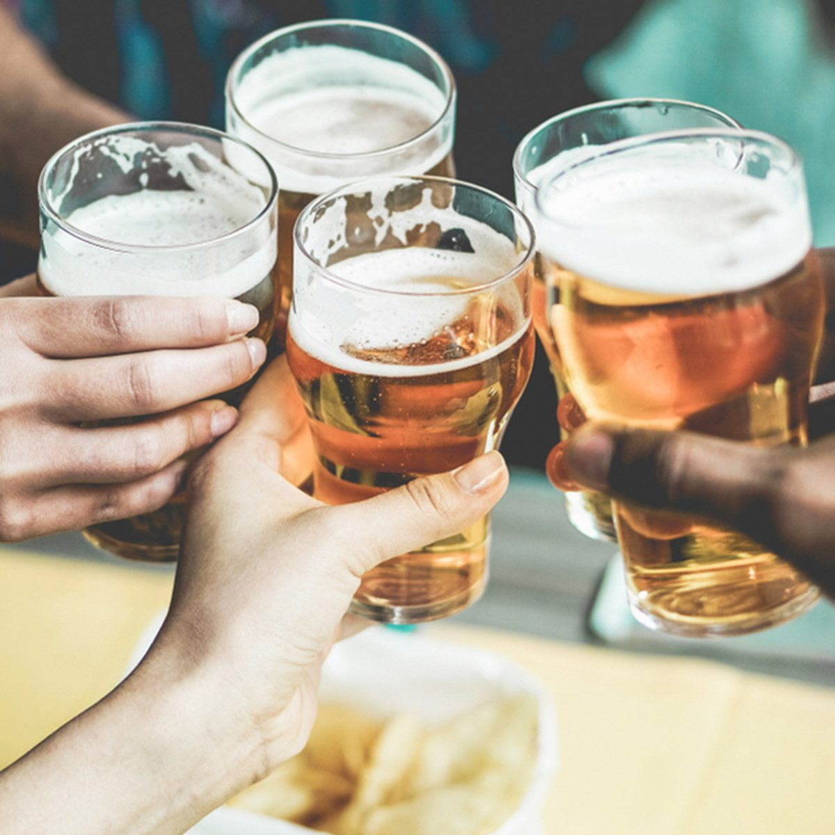 Group of friends enjoying a beer in brewery pub - Young people hands cheering at bar restaurant