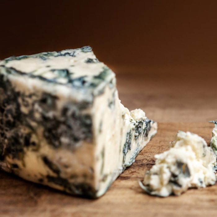Blue cheese Gorgonzola on a rustic wooden background.