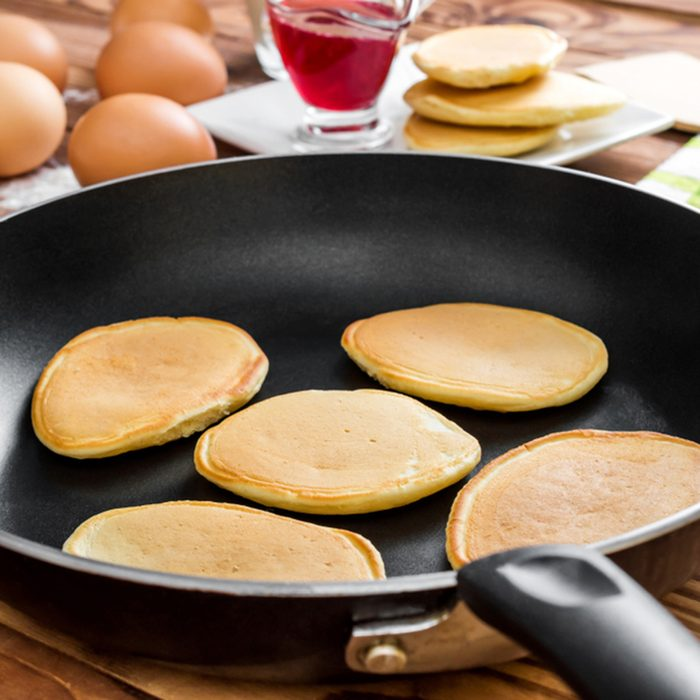 Pan with pancakes and ingredient for cooking pancakes on the table.