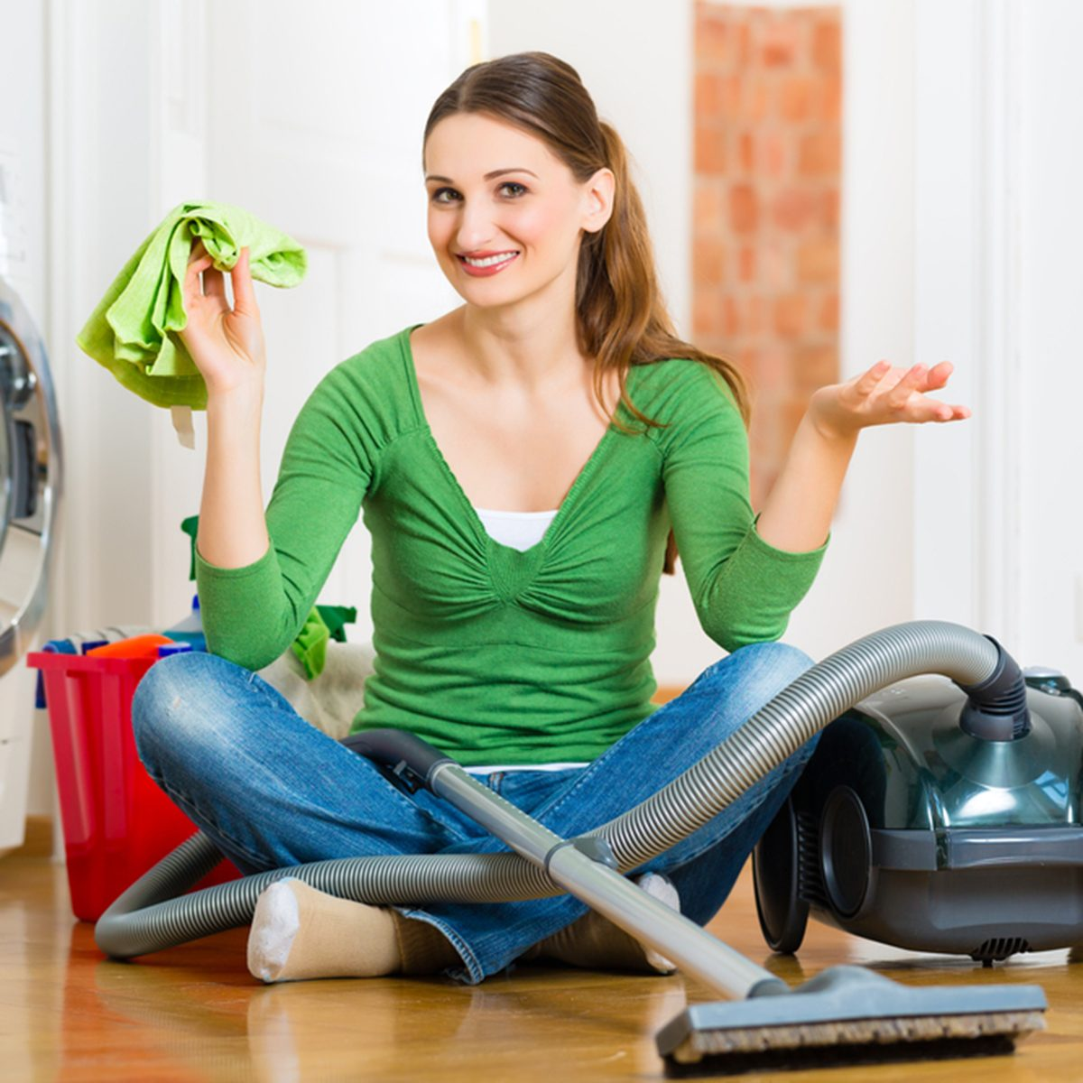Young woman cleaning at home, she has a cleaning day and using a vacuum cleaner cleaning products and a bucket