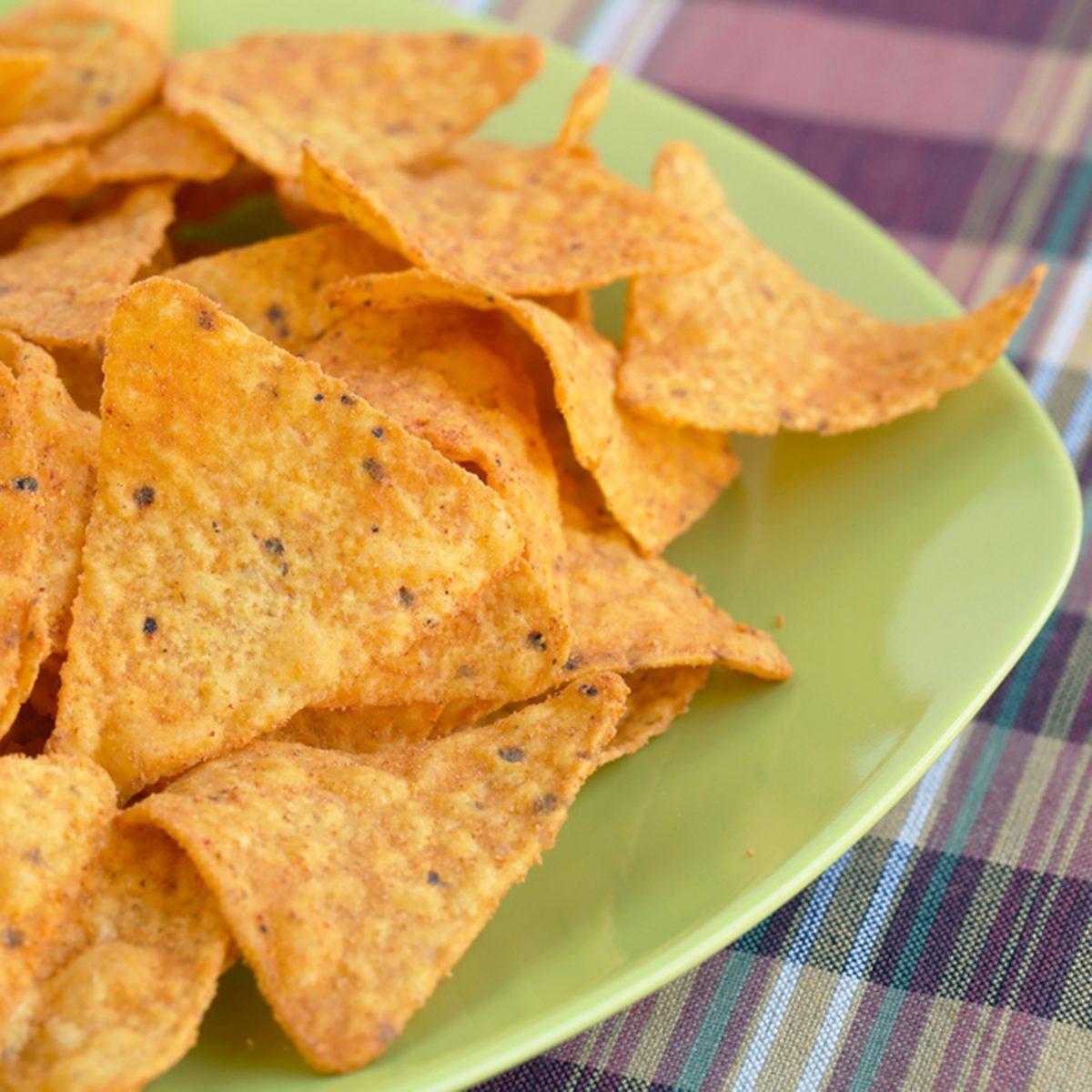 Heap of nachos on green plate.; Shutterstock ID 142006165; Job (TFH, TOH, RD, BNB, CWM, CM): TOH