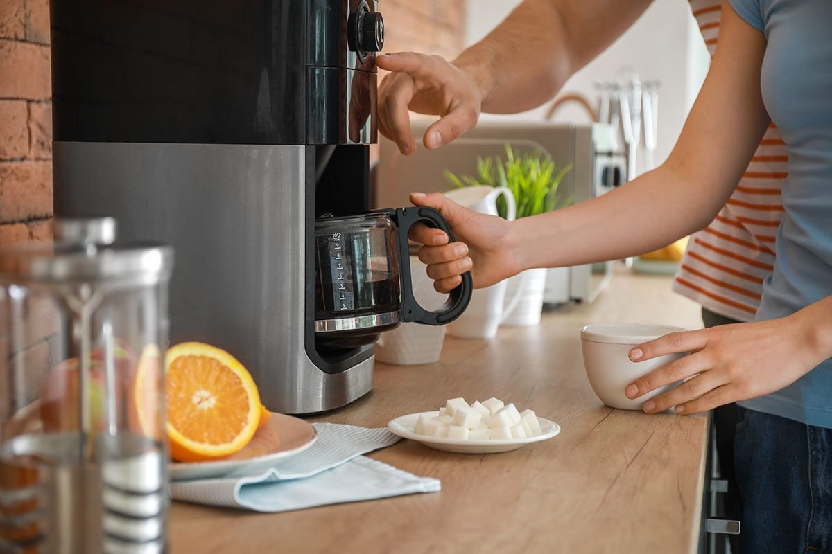 Young couple using coffee machine in kitchen; Shutterstock ID 1426223720; Job (TFH, TOH, RD, BNB, CWM, CM): Taste of Home
