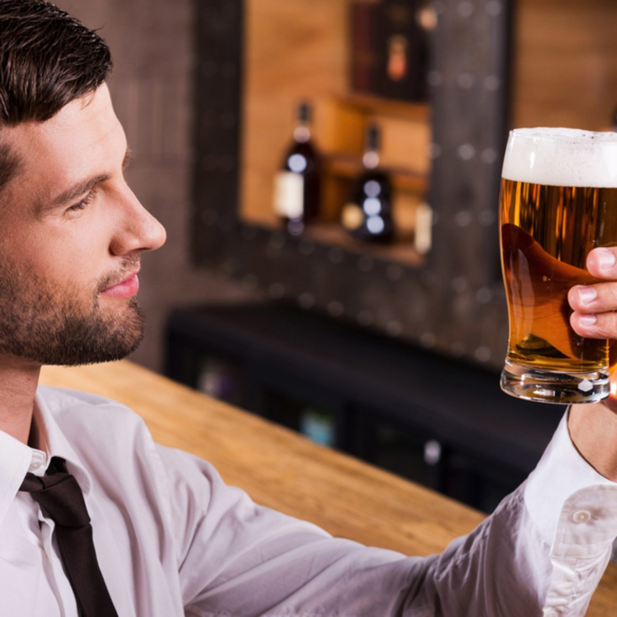 Side view of handsome young man in shirt and tie examining glass with beer and smiling while sitting at the bar counter