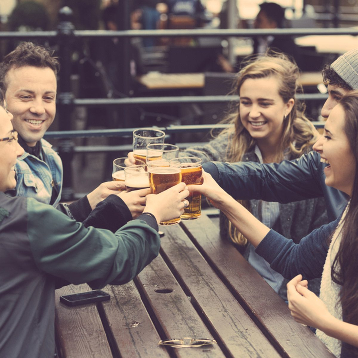Group of friends enjoying a beer at pub in London, toasting and laughing.