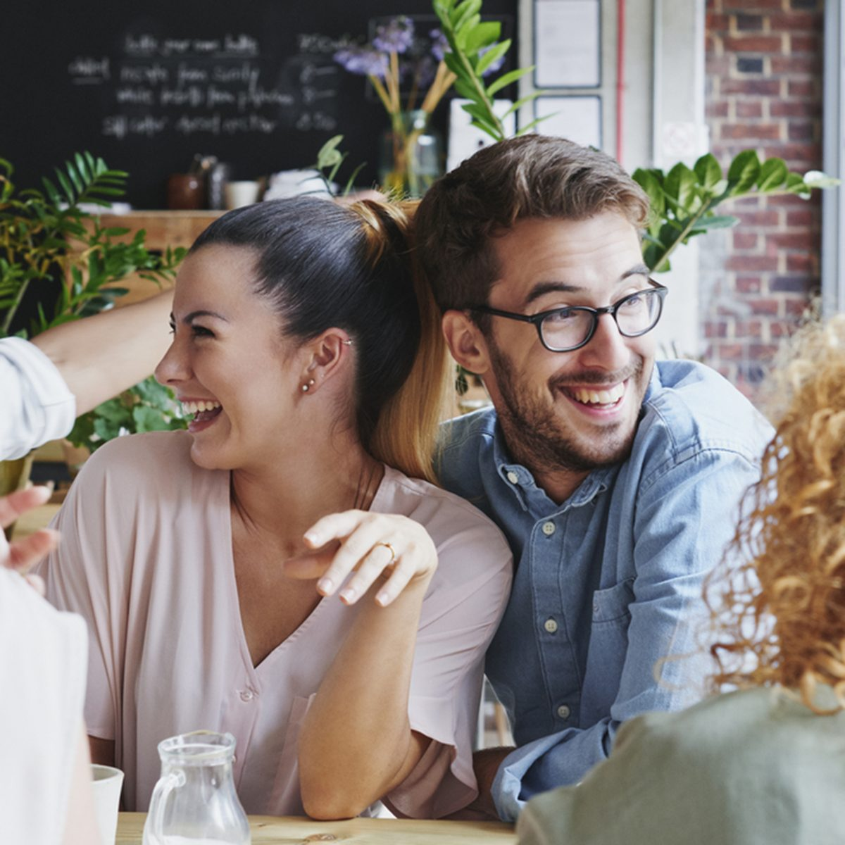 Woman showing engagement ring to friends in cafe celebrating