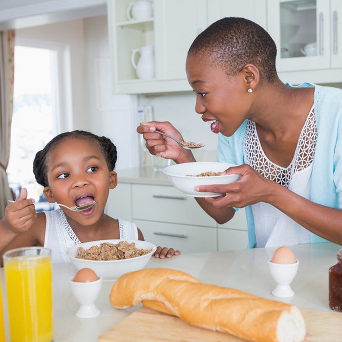 Portrait smiling mother and daughter eating together at home in the kitchen