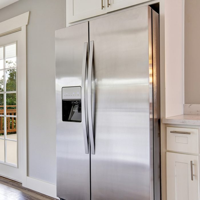 Bright kitchen room with steel appliances and granite tops.
