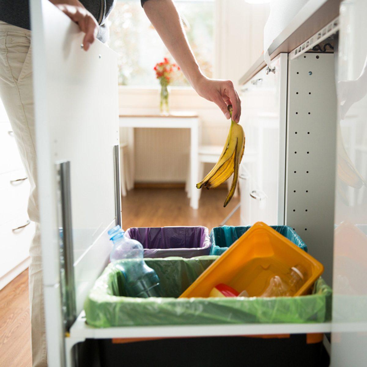 Woman putting banana peel in recycling bio bin in the kitchen.
