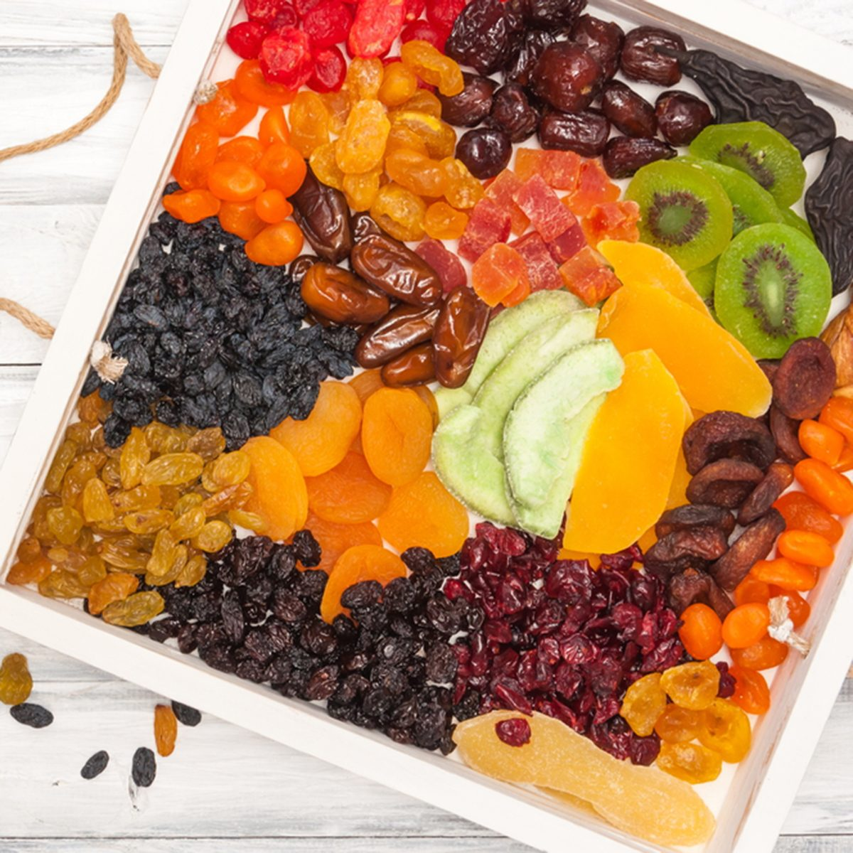 Mix of dried and sun-dried fruits, dried fruits in a wooden box on a white wooden background.