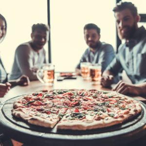 Pizza time. Close-up of tasty pizza on the table, with a group of young smiling people resting in the pub.; Shutterstock ID 641163061; Job (TFH, TOH, RD, BNB, CWM, CM): Taste of Home