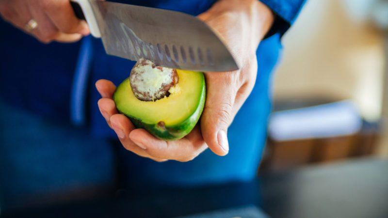 Fresh Avocado Being Cut In Half