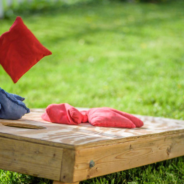 playing cornhole in backyard throwing bag in air; Shutterstock ID 668982058