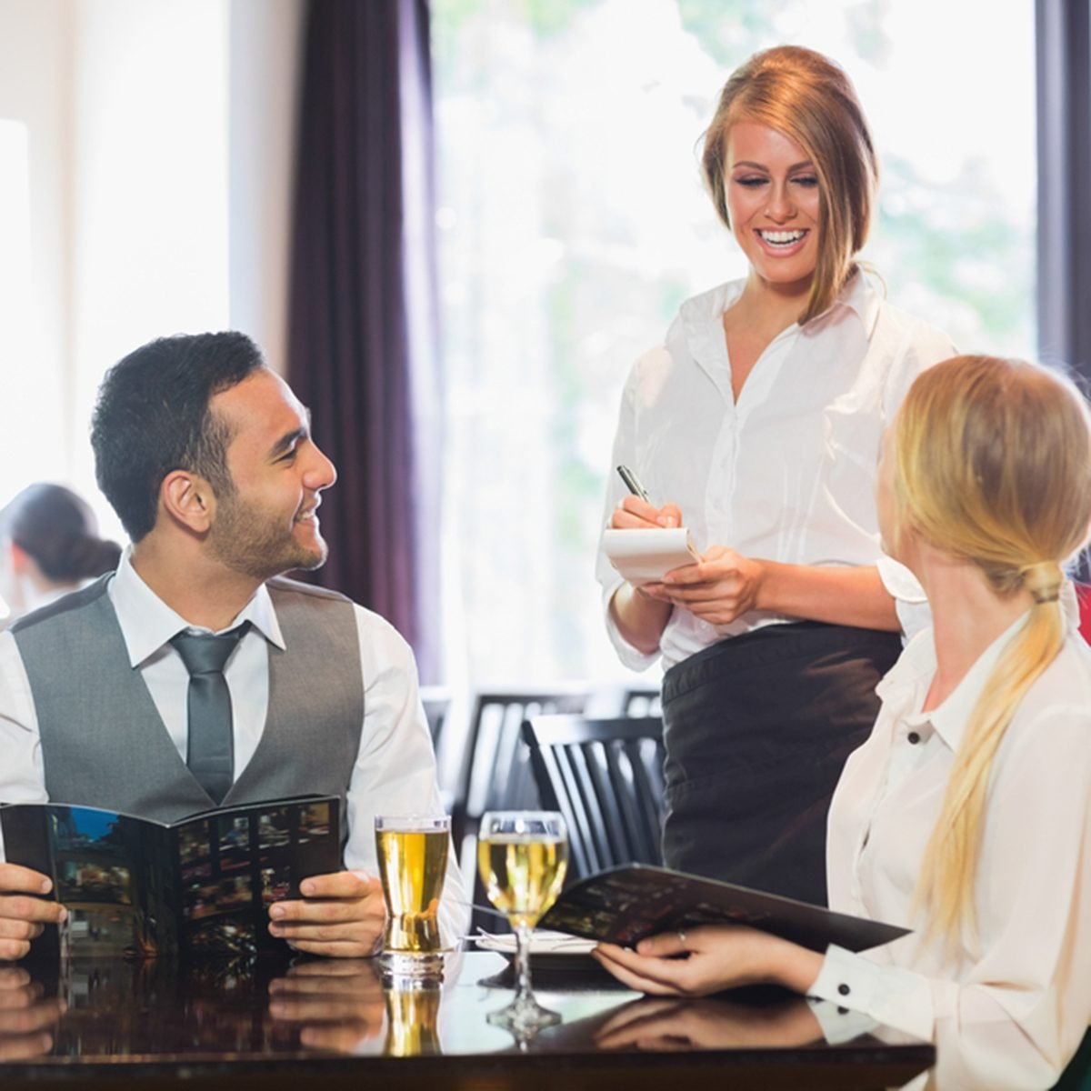 Smiling business people ordering dinner from pretty waitress