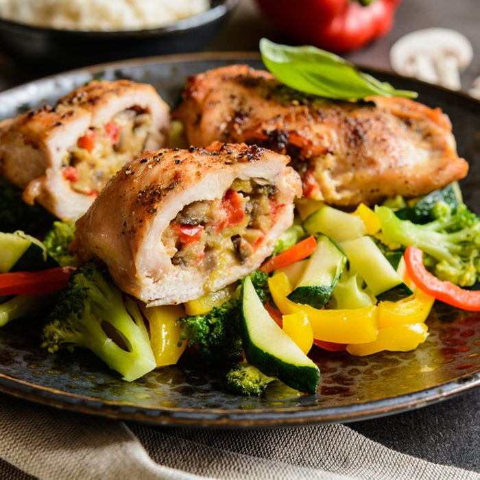 Roasted chicken breasts stuffed with mushrooms, green onion, pepper and sheep cheese, garnished with steamed vegetable and rice