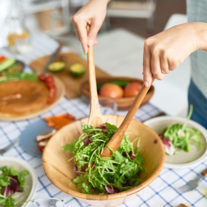 Closeup of young woman mixing green salad in wooden bowl at table with wholesome food while preparing family dinner; Shutterstock ID 734792491; Job (TFH, TOH, RD, BNB, CWM, CM): TOH Superfoods