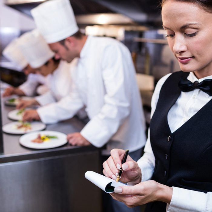 Waitress with notepad in commercial kitchen and chefs preparing food in background