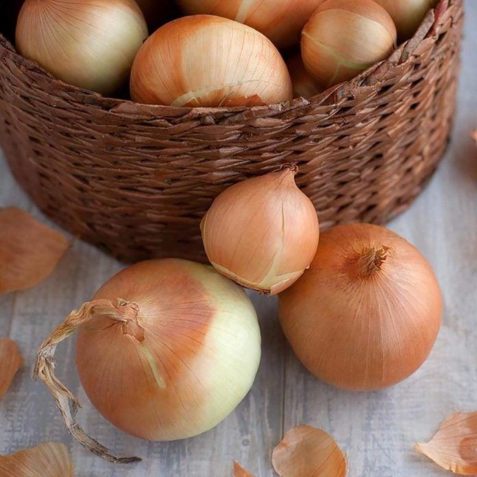 Large onion harvest in a wicker basket.