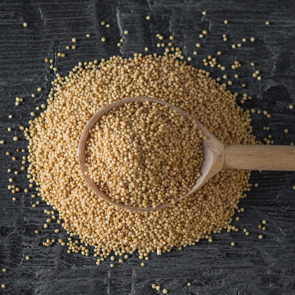 A pile of amaranth seeds and a wooden spoon on a dark wooden table.
