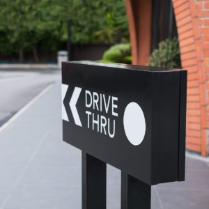 Drive thru sign with shop and road background.