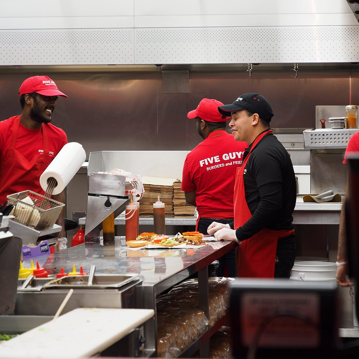 Closeup of crews working at Five Guys burger chain busily, Avenue des Champs-Élysées, Paris, France