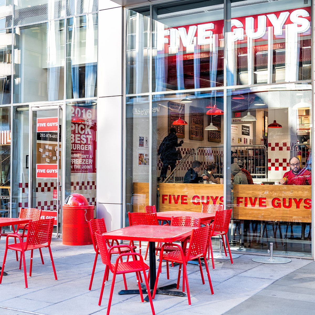 Five Guys restaurant, store burger chain entrance in District of Columbia with chairs, tables, outside, outdoor sitting area, people inside eating